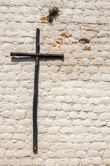 A rustic wooden cross on a white brick wall