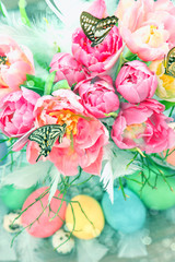 pink tulip flowers, butterflies and colored eggs