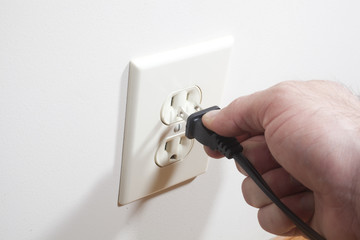 A hand putting a two prong plug into a wall socket.