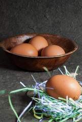 Raw eggs in wooden bowl on gray background