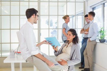Pregnant businesswoman talking with colleague sitting at desk