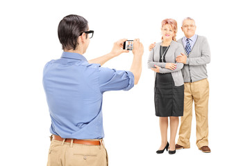 Young man taking picture of a mature couple