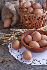 Eggs in wooden bowl with a little basket and linen sack