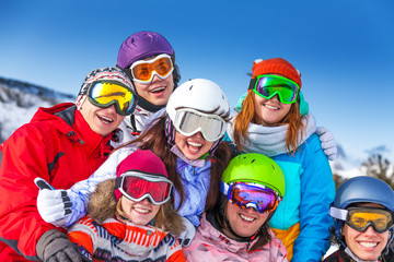 Seven smiling friends wearing goggles