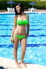 Happy girl in swimming pool in the summer posing
