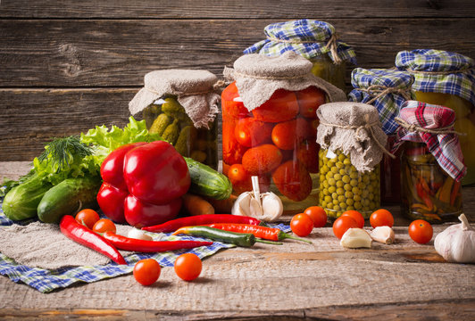 Preserved  and fresh vegetables on wooden background