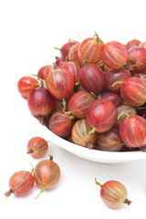 red gooseberries in a bowl isolated on white