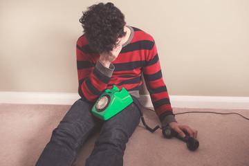 Sad man receiving bad news on telephone