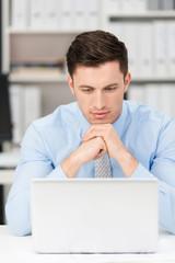 manager schaut konzentriert auf laptop
