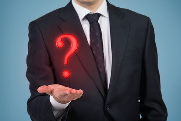 Businessman holding a red question mark, blue background