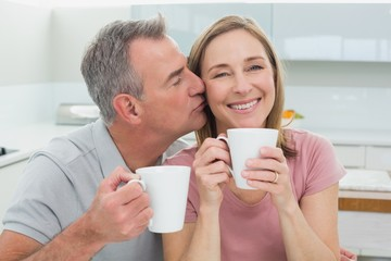 Man kissing a happy woman while having coffee in kitchen