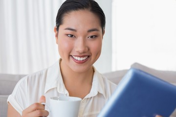 Smiling woman sitting on couch using tablet pc having coffee