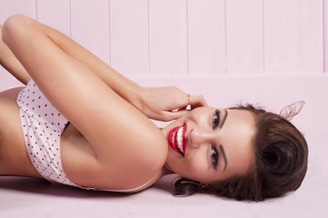 Beauty smiling pinup girl lying on the floor