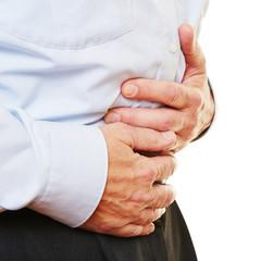 Mann mit Bauchschmerzen hält Bauch