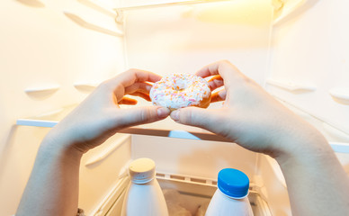 photo of female hand taking donut from refrigerator