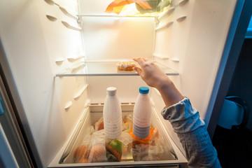 portrait of female hand taking donut from fridge