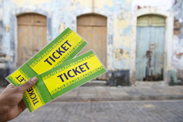 Brazilian Hand Holding Two Tickets on the Street