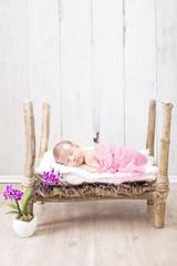 Newborn Kleines Mädchen schläft in einem Holzbett