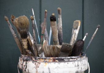used natural brushes in bucket with wooden background