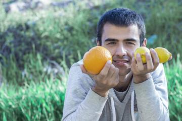 Man holding lemons and oranges