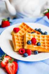 Belgian waffles with berries on rustic background
