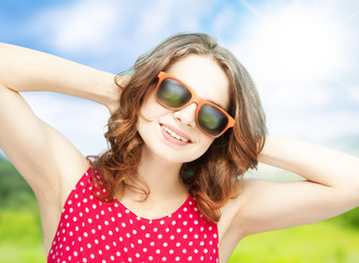 beautiful girl in sunglasses  on summer background in soft focus