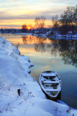 Wall Mural - Winter sunset on the river with a boat