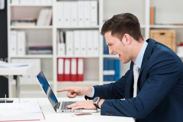 genervter geschäftsmann zeigt auf laptop