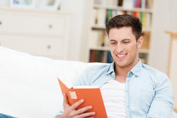 mann liest ein buch auf dem sofa