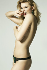 sexy topless woman in panties with arm covering breasts, studio
