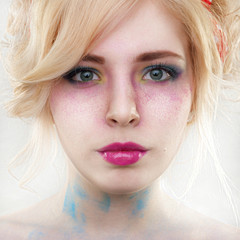 Fantasy woman with bright make-up and powder on face on grey bac