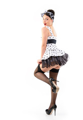 Pinup girl on high heels in spotted dress stocking, full length
