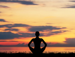 Silhouette of a young woman meditating on a sunset