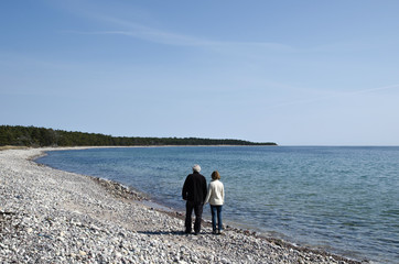 Senior couple walks along coast