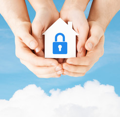 hands holding paper house with lock