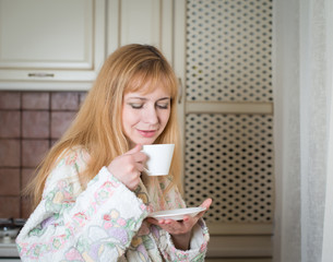 Woman with cup of coffee or tea in the kitchen. Morning coffee.