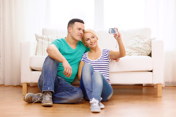 smiling couple taking picture with digital camera