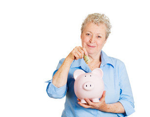 Older woman happy with savings, depositing money in piggy bank