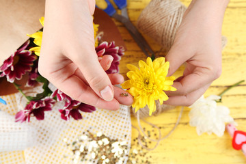 Female hands composing beautiful bouquet, close-up. Florist at