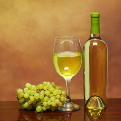Wine Bottle and Glass of White Wine with Fresh Grapes over beige