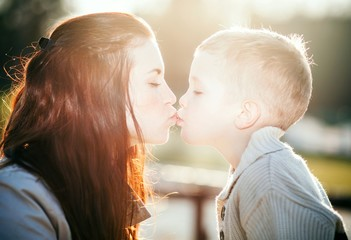 Wall Mural - Young mother kissing child outdoor