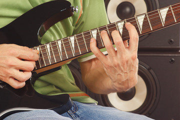 Hands of man playing the electric guitar closeup