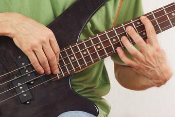 Hands of man playing the electric bass guitar closeup