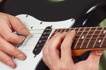 Rock guitarist put fingers for chords on electric guitar closeup
