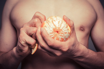 Closeup on athletic man peeling an orange