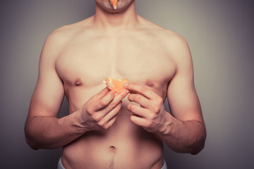 Athletic shirtlss man peeling an orange