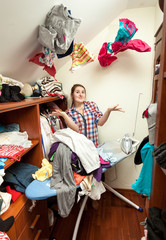 housewife in dressing room with clothes flying around