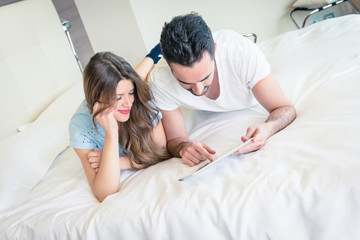 Couple with tablet computers in their bedroom - stock