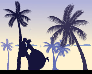 Wedding couple between the palms on the beach