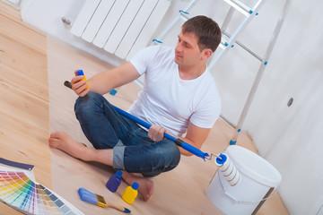 youg painter sitting on floor holding paintroller small bottle o
